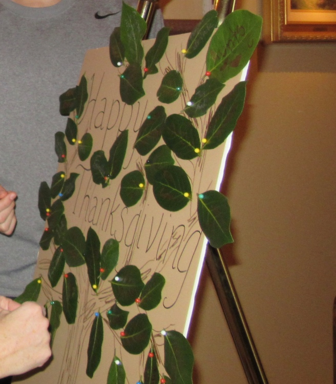 Family members arranging gratitude-covered bay leaves during the appetizer hour.
